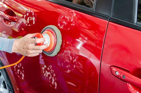 Die Hand des Mechanikers hält ein Autolackwerkzeug. Beschichteter Autolack mit rotem Autowachs Standard-Bild