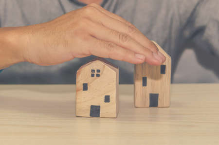 business concept - man with a hand to protect the house.Insurance coverage for home security