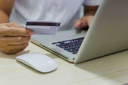 Man Shopping Online Using Laptop With Credit Card.Hands holding credit card. Imagens