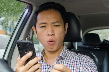 Asian man wearing a plaid shirt looks at smart phone in a car. Stock Photo