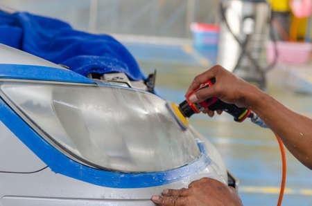 Car headlight cleaning polishing machine at car service.
