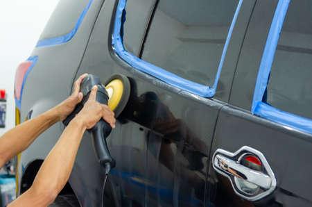 Man hand holding a car polish machine. Car detailing Buffing and wax.