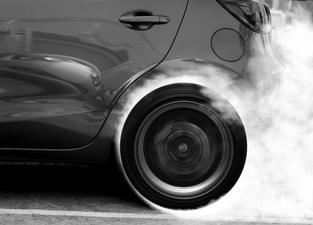 super car: Super car wheel drifting and smoking on track with black and White Color Stock Photo