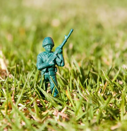 plastic soldier: Plastic toy soldier standing in green grass with an automatic rifle