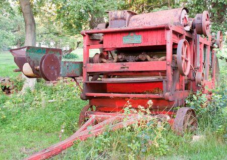 derelict: Derelict old farming machine standing amongs weeds Stock Photo