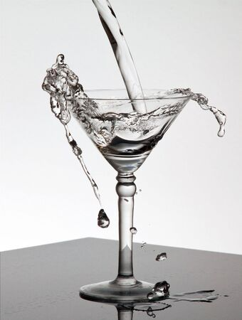 Water pouring into a Martini glass standing on a shiny surface and spilling