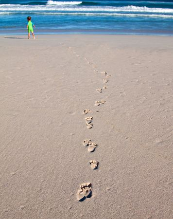 Footprints of a child on the beach going towards the breakers