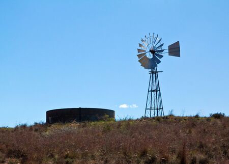 Windmill in the bright African sun against a bright blue sky photo