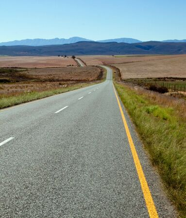 Road over farm lands in South Africa towards distant mountains photo