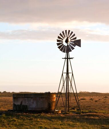 Windmill at sunrise on a farm with a water dam photo