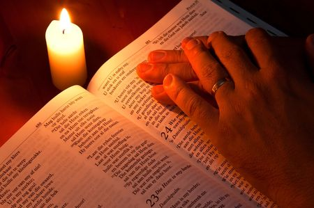 folded hands: Bible by candle light with hands resting on it