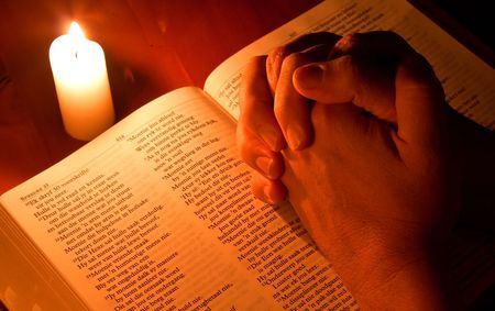 christian candle: Bible by candle light with hands folded in prayer Stock Photo
