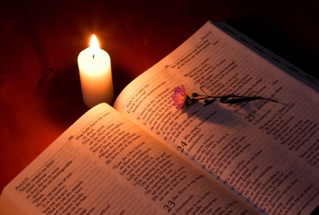 Bible by candle light on wooden table with small flower photo