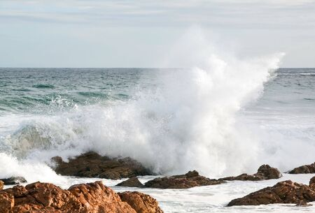 Wave crashing over brown rocks in the ocean in bright sunlight photo