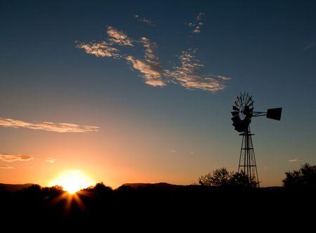 rancho: Silueta de un molino de viento al atardecer en el Karoo  Foto de archivo