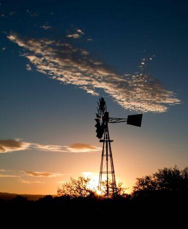 windmills: Silueta de un molino de viento al atardecer en el Karoo  Foto de archivo