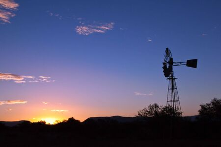 Windmill spinning fast at sunset with lovely orange colours in the Karoo photo