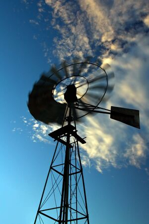 Windmill at sunset in the Karoo  spinning fast against a blue sky photo