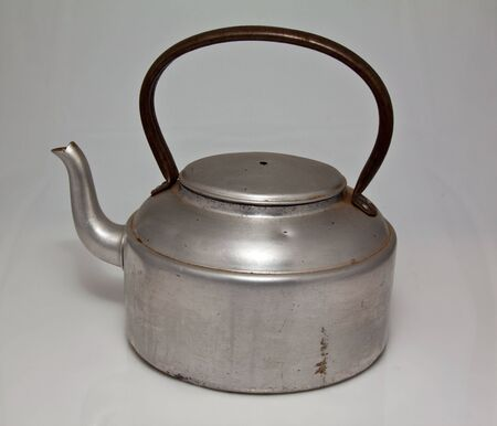 Old silver kettle with black handle, used to boil water over an open fire photo