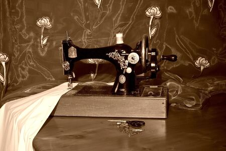 gold table cloth: Old style sewing machine, sewing a white cloth