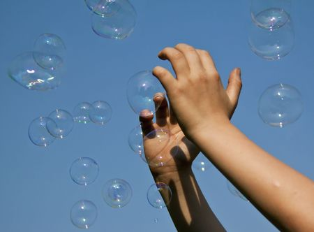 Hands catching bubbles against a blue sky in sunshine Stock Photo - 8038775