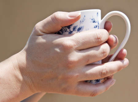 chinaware: Hands holding cup around to drink