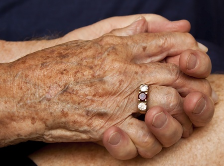Old couple holding hands with ring on finger photo