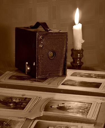 Old camera and album by candlelight in sepia