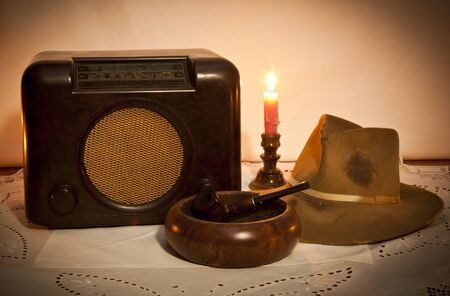 Old radio, hat, pipe and ashtray by candle light on table photo