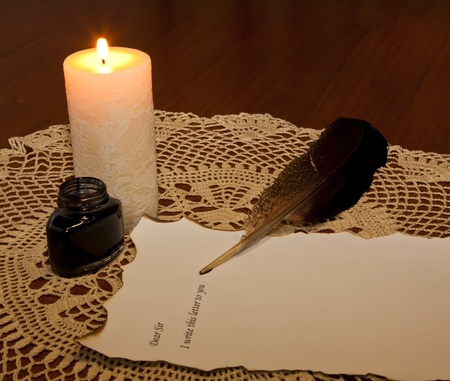 ink pot: Quill, ink pot and candle to write letter in low light
