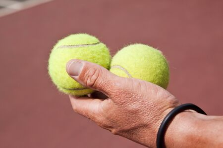 Tennisplayer holding two balls in his hand on court photo