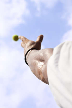 Tennisplayer trowing up a ball with his hand to serve blue sky photo