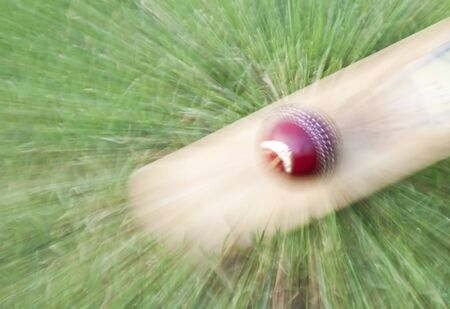 Cricket ball on bat zoom warped on green grass Stock Photo