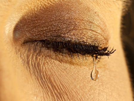 Macro closeup of a female eye with teardrop in soft light