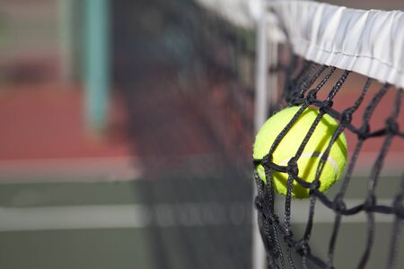 Tennisball hitting the net on a court point lost