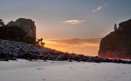 Sunrise landscape on the beach with rocks and cliffs clouds Stock Photo