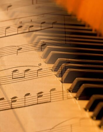 Sheet music blended over piano in soft light blurred Stock Photo