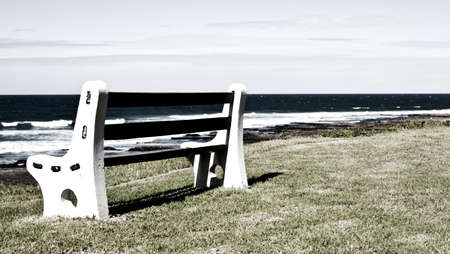Bench on grass next to the ocean in grunge infrared effect photo