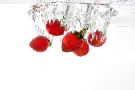 Strawberries dropped into water splash white background Stock Photo