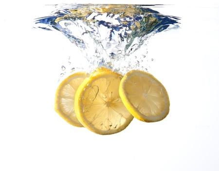 lemon slices: Fette di limone cadere in acqua spruzzata bianca Archivio Fotografico