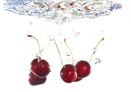Red cherries falling into clear water with ripples