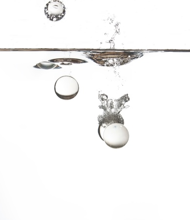 Clear glass balls falling into water creating a splash