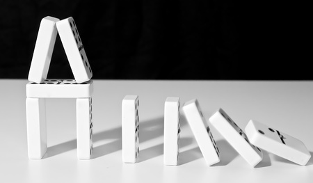 boardgames: Domino house standing on white surface falling