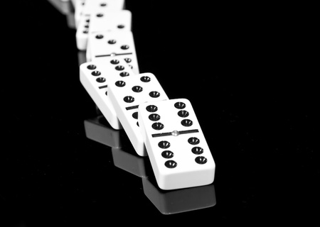 boardgames: Fallen dominoes lying on black shining surface creating a reflection