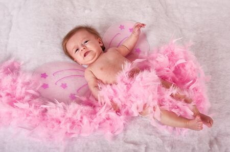 Baby girl on soft surface with pink fairy wings photo