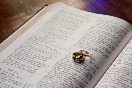 Wedding rings lying on Bible symbolizing the beginning of a marrage photo