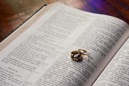 marrage: Wedding rings lying on Bible symbolizing the beginning of a marrage Stock Photo