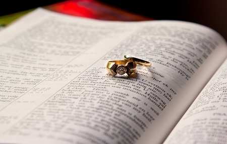 Close up of wedding rings lying on an open Bible photo