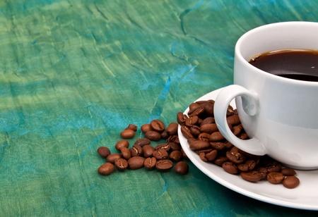 ejotes: Una taza de caf� negro con granos de caf� marr�n alrededor de un mantel verde