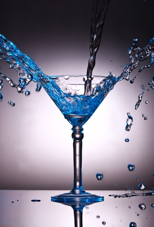 Martini glass with water splash with a blue color tint